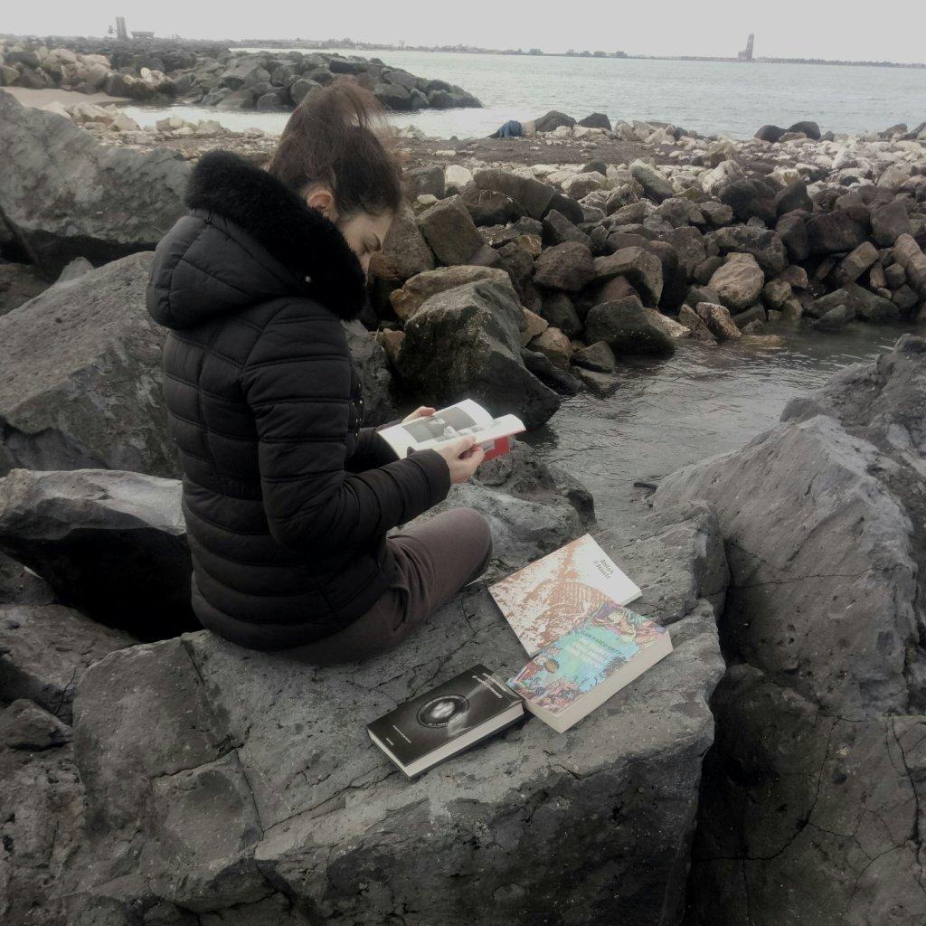 """Nel calduccio del suo studiolo, Ilaria Petrarca sfoglia i libri ricevuti in premio per il gioco-concorso """"Fermo-paesaggio"""""""
